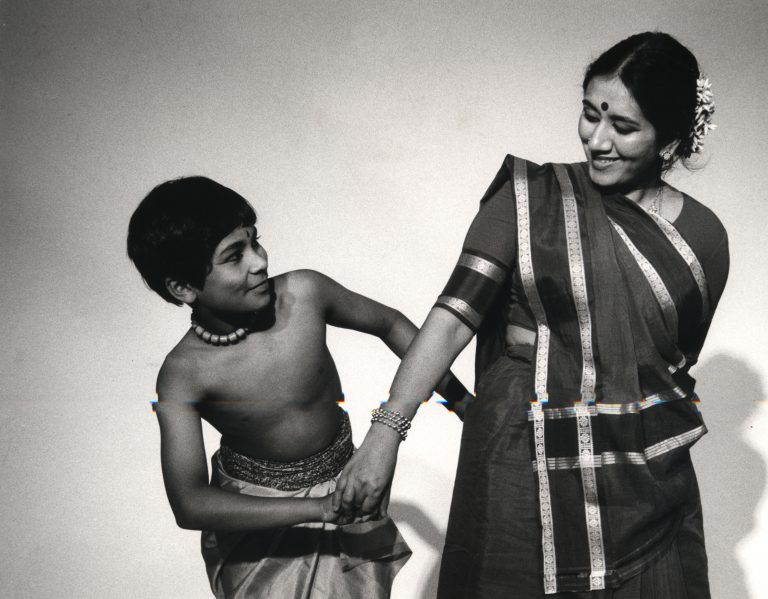 Woman and young boy with intertwined arms