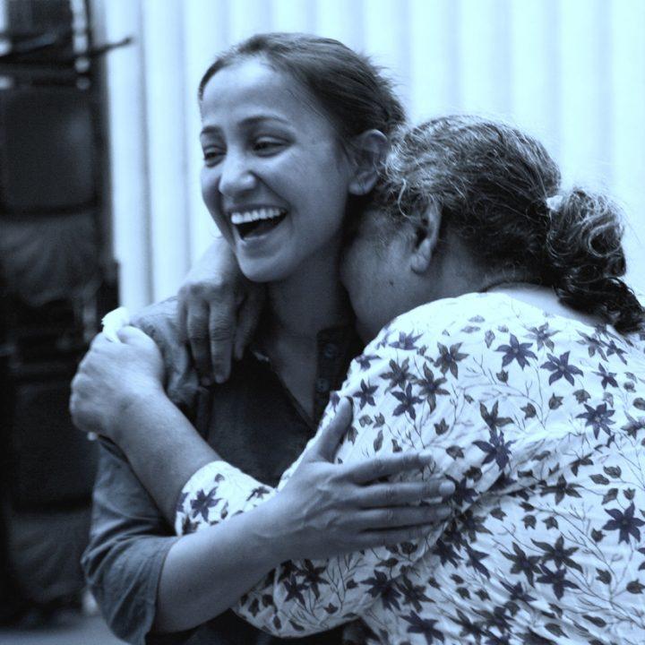 Two women laugh and hug