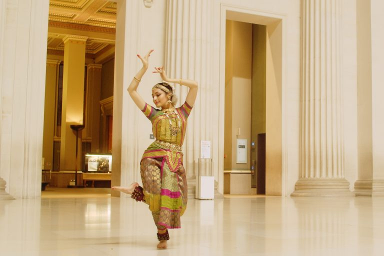 Ornately dressed South Asian dancer depicted dancing in a museum