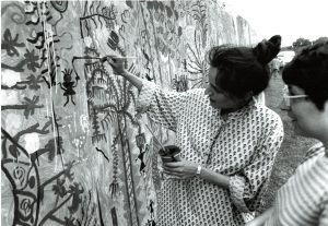 Two women painting an outdoor mural
