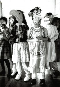 Primary school children hold masks during a dance workshop