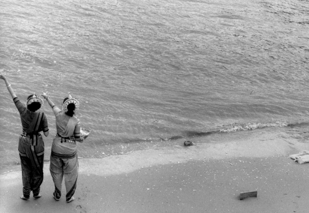 Two dancers stand on the shore facing the water