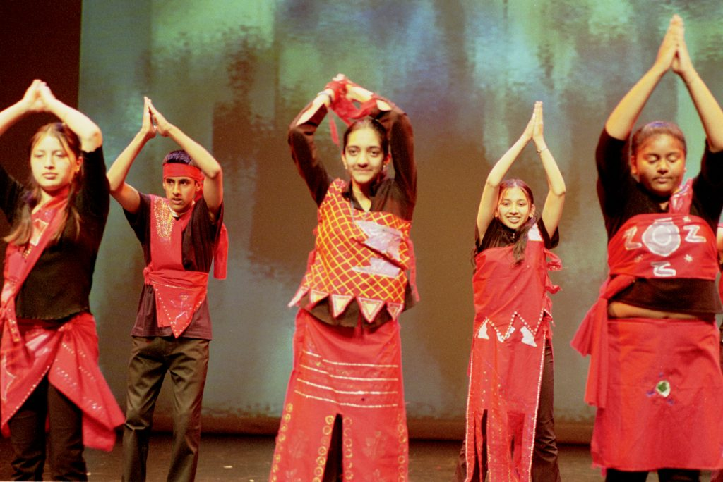 Group of young people performing in bright costumes