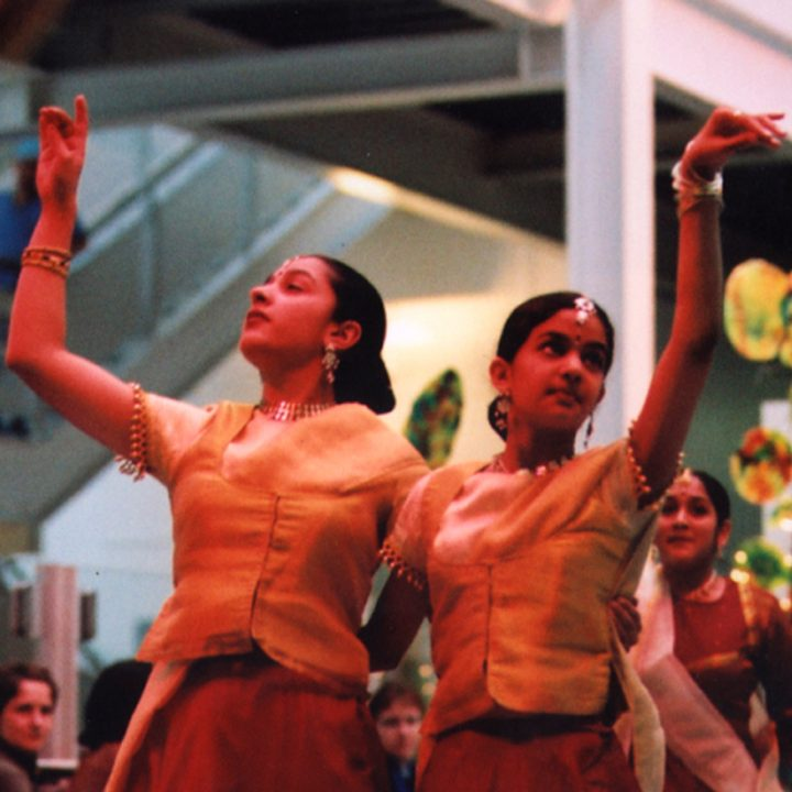 South Asian dancers perform to a crowd